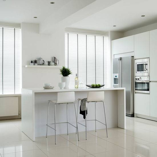 White taped faux wood blinds in big kitchen windows