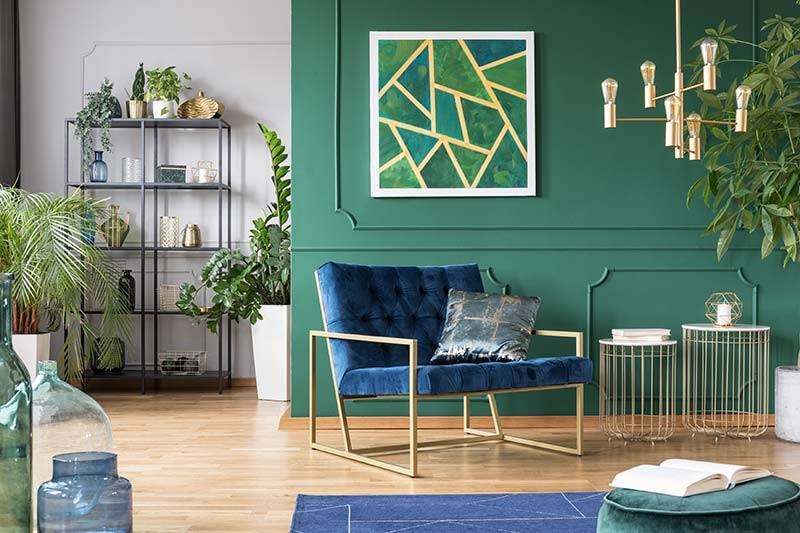 Living room with green walls, blue velvet sofa and houseplants