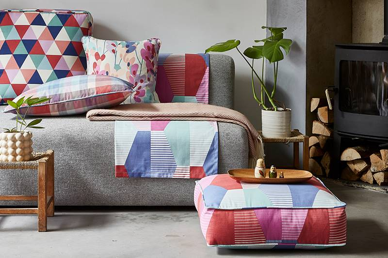 Close up of colourfull patterned cushions and throws in a living room