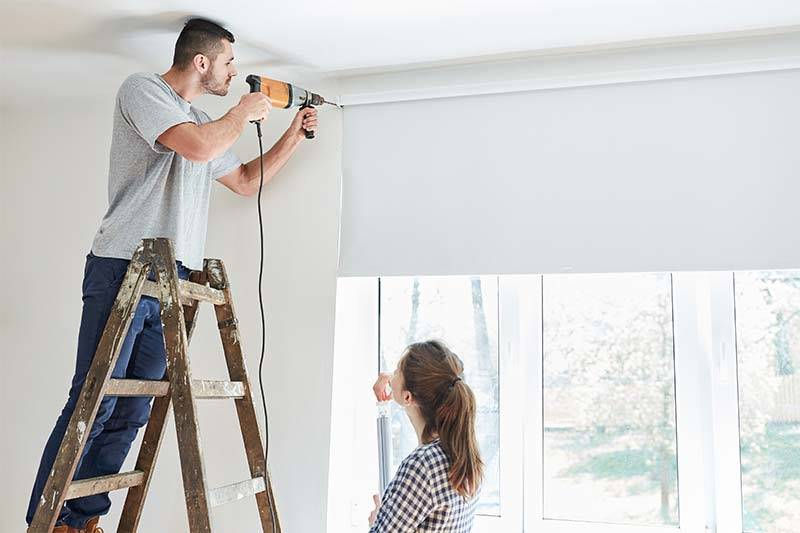 Young couple as a home improvement during the installation of a window roller blind while renovating