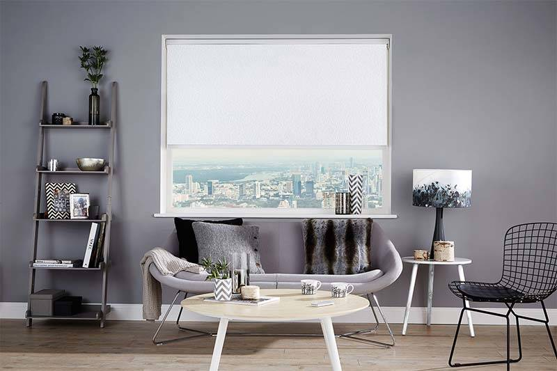 Electric white roller blind in a living room with a remote control on the table