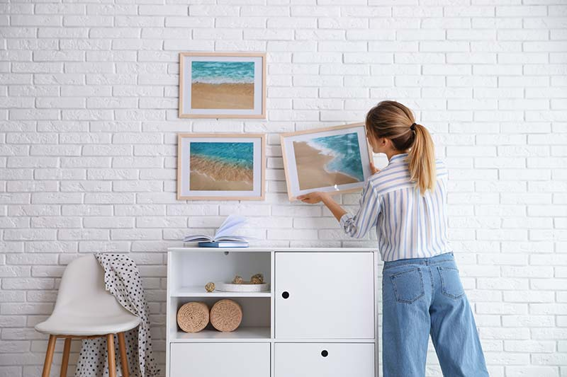 Young lady hanging picture on white brick wall in room