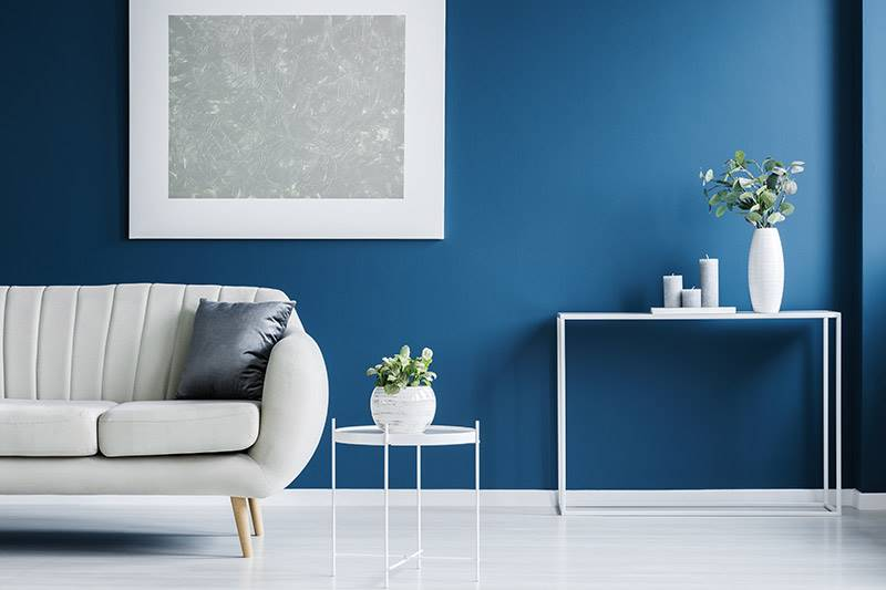 Living room with blue wall and light coloured interior