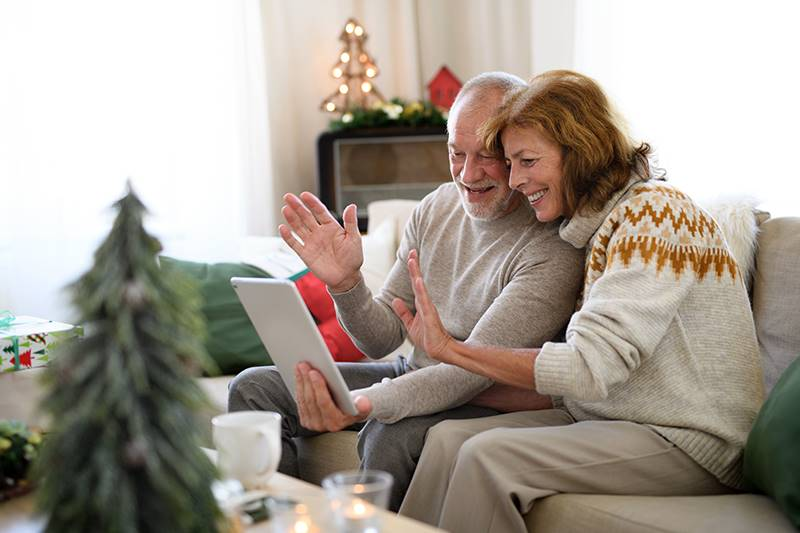 A mature couple talking to their family on iPad