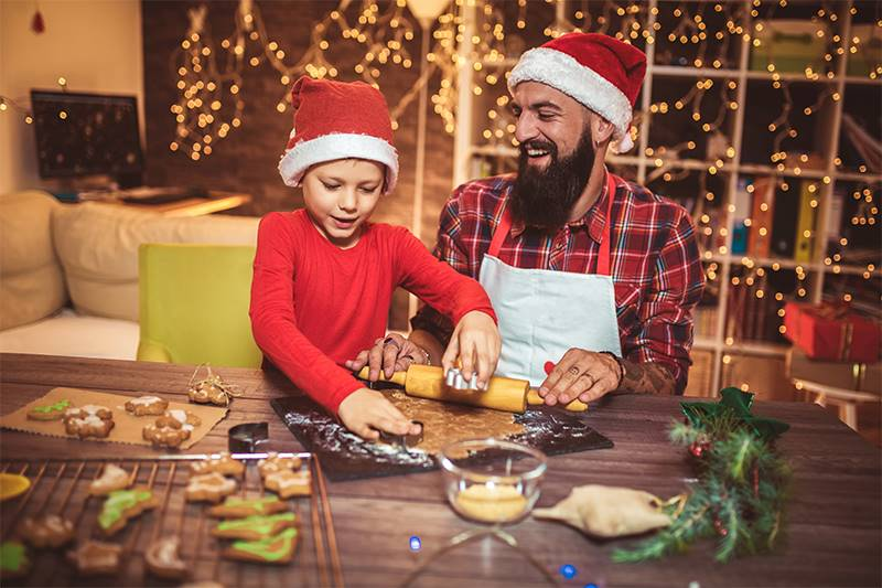 Father and son making Christmas cookies at home