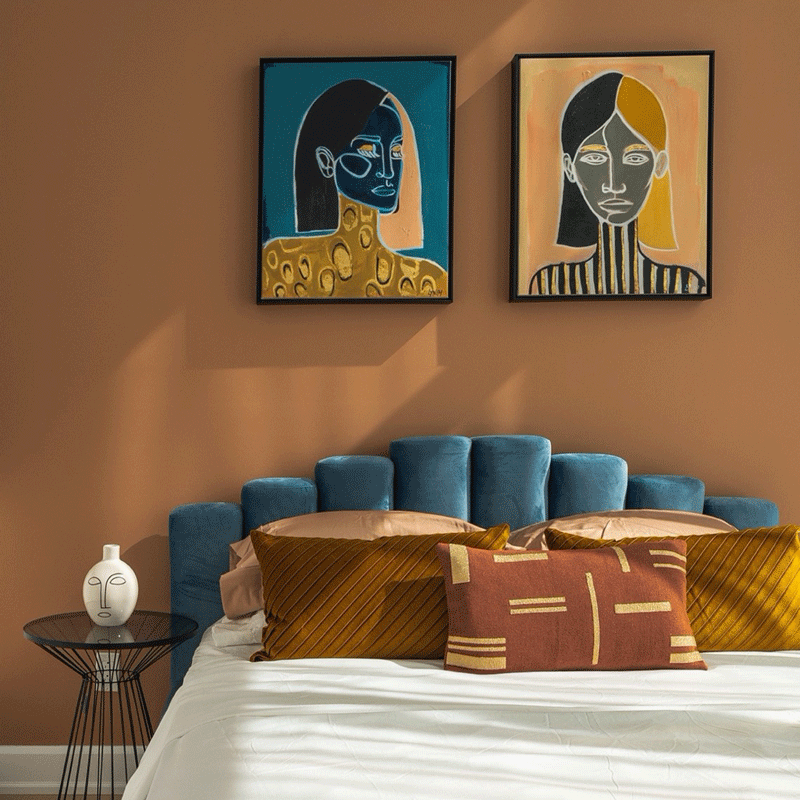 Bedroom with a blue velvet bed and modern artwork