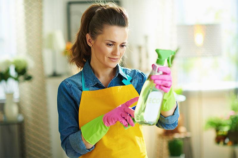 Young woman with spray bottle of eco friendly cleaning supplies reading instruction in the modern house.