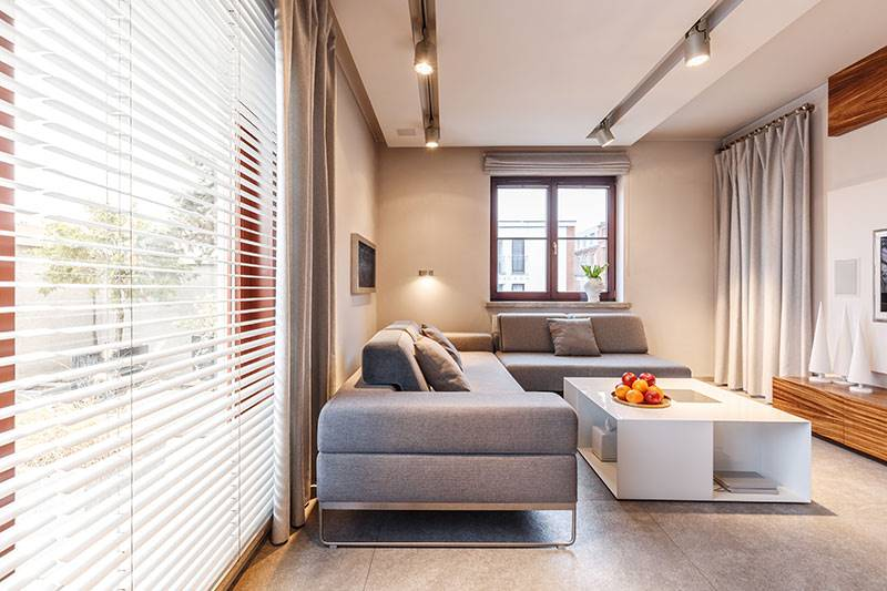 LED lights in modern living room with faux wood venetian blinds and grey curtains