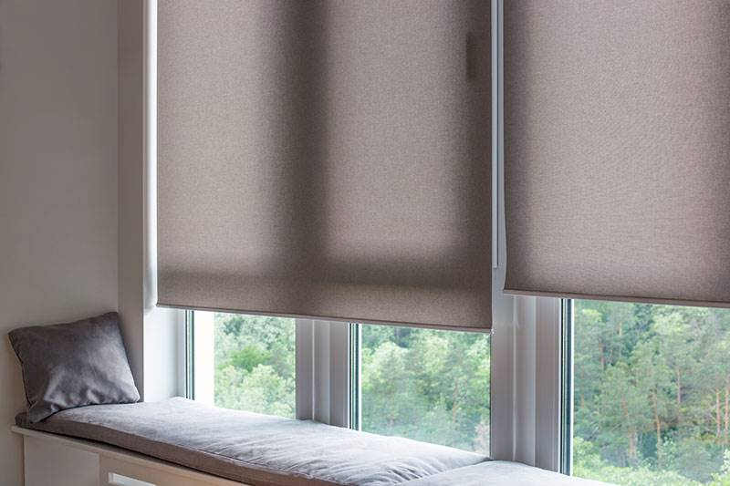 Grey eco friendly roller blind in a big living room window