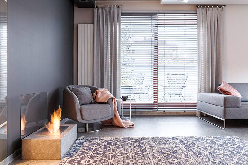 Grey thermal curtain and faux wood blinds in a full height living room window
