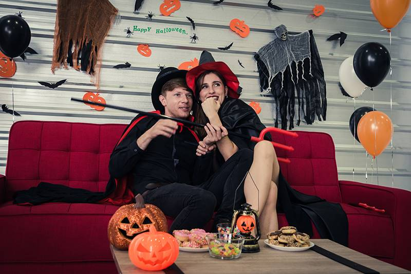 Young couple watching a horror movie in television and sitting on sofa in halloween party