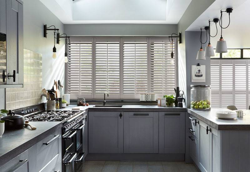 Full heigh faux wood shutters in a kitchen window
