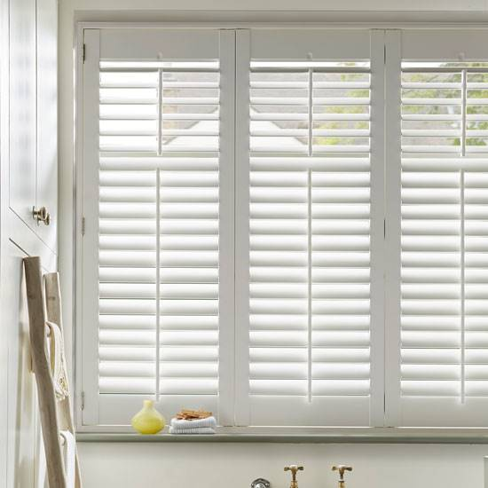 Faux wood white shutters in a bathroom window