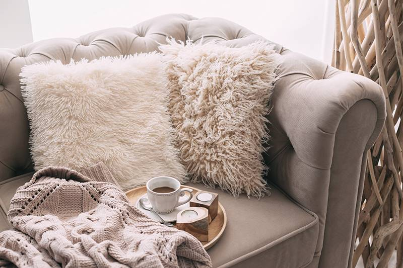 Cozy winter sofa with fur cushions and coffee.