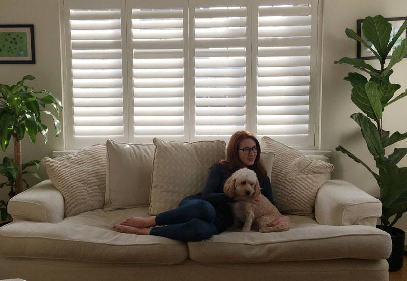A woman sitting on a sofa with a dog next to white full height shutters