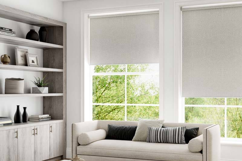 Grey blackout roller blinds in large living room windows