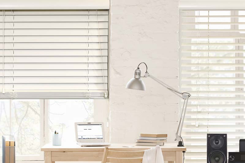 Close up of real wood white wooden blinds in a study room
