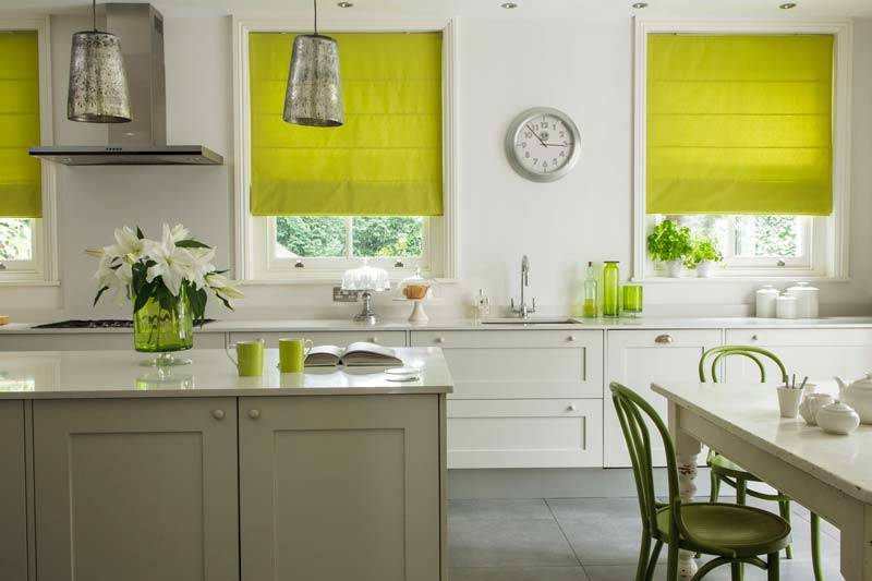Plain green roman blinds in kitchen window