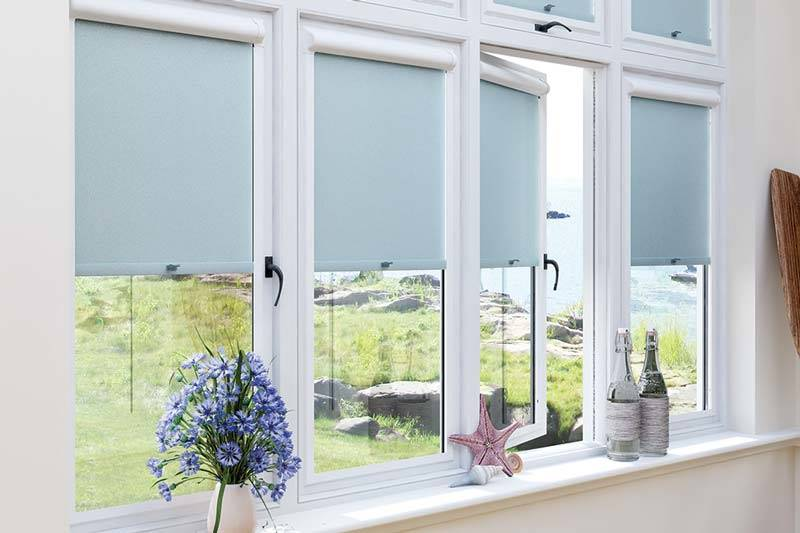 Close up of blue perfect fit roller blinds in conservatory windows