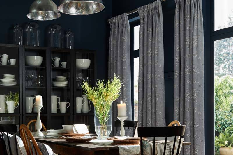 Full length patterned blue curtains in a dining room