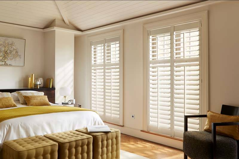 Full height white shutters in big bedroom windows