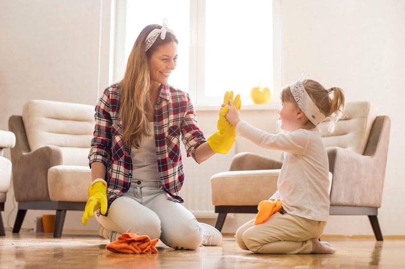 Mum and daughter cleaning in home