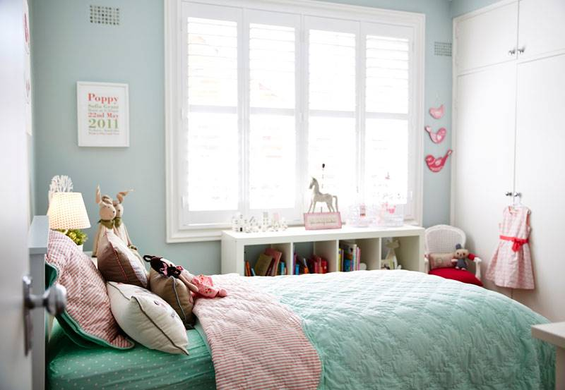 Full height white shutters in a children's room