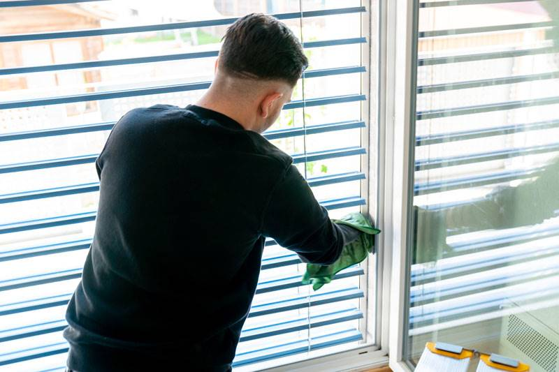 Man cleaning wooden blinds