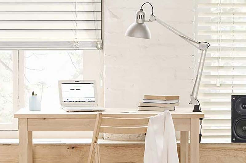 Close up of white wooden blinds in a home office