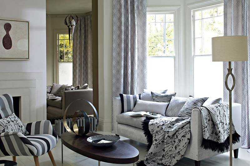 Full length grey patterned curtains in a big bay living room window