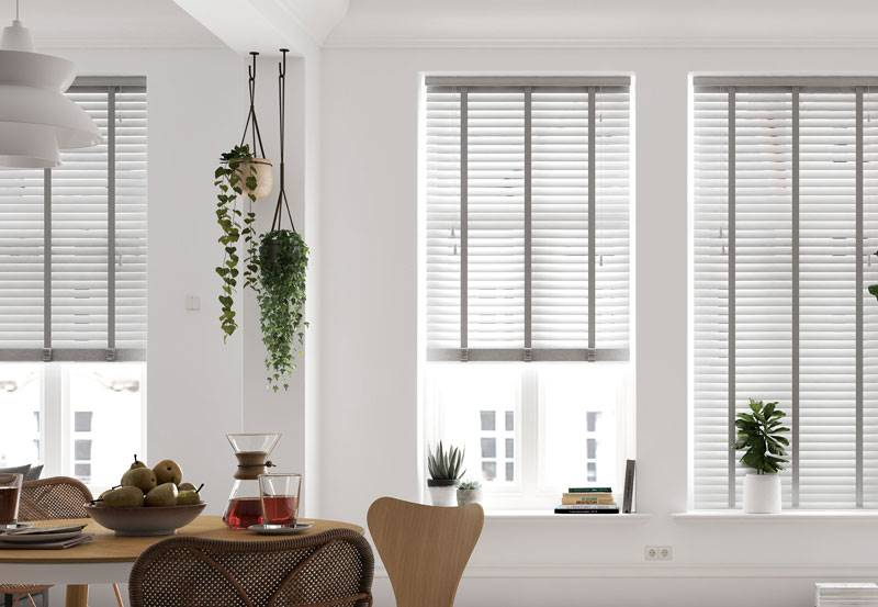 White taped faux wood blinds in kitchen windows