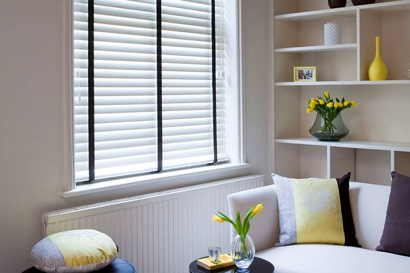 Taped Faux wood blinds with contrasting tapes in a living room window