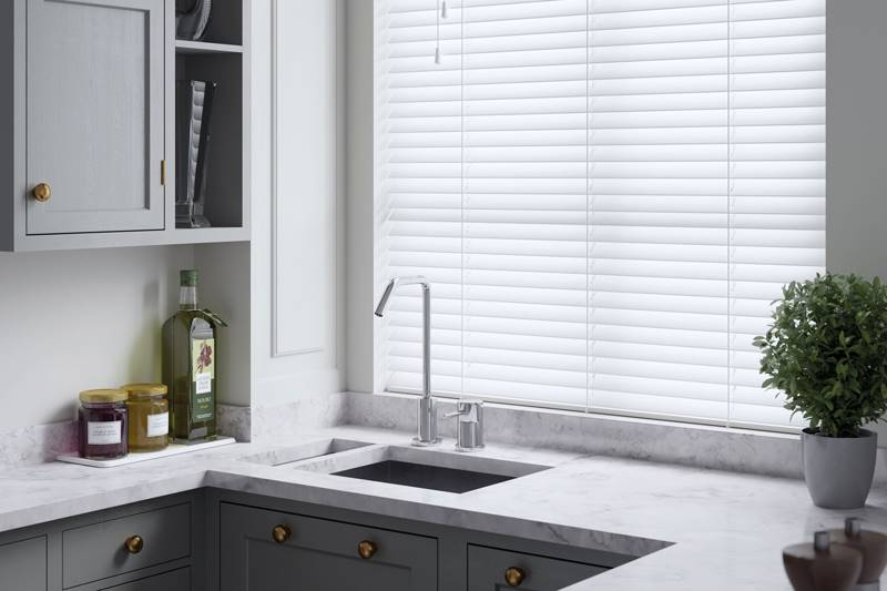 White faux wood blind in a kitchen window above a sink