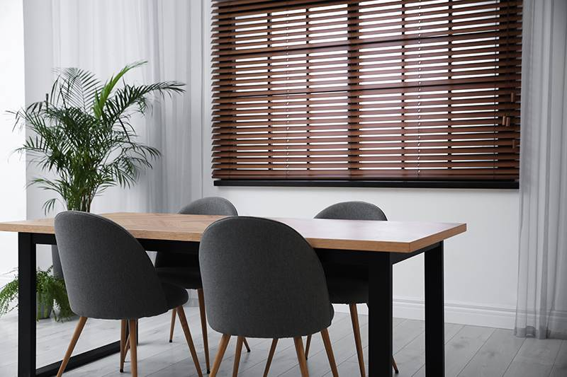 Dark real wood blind in a dining room window