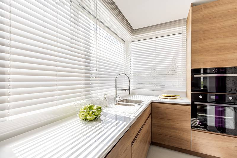 White faux wood blinds in a big kitchen window above a sink