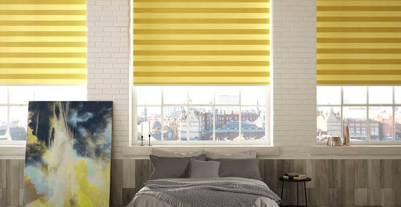 Image shows a bedroom with three large windows. The bedroom contains a bed with grey sheets, an abstract canvas with blue, white, and yellow, and two blue and yellow cushions on the floor. The windows are adorned with bright yellow horizontal striped blinds.
