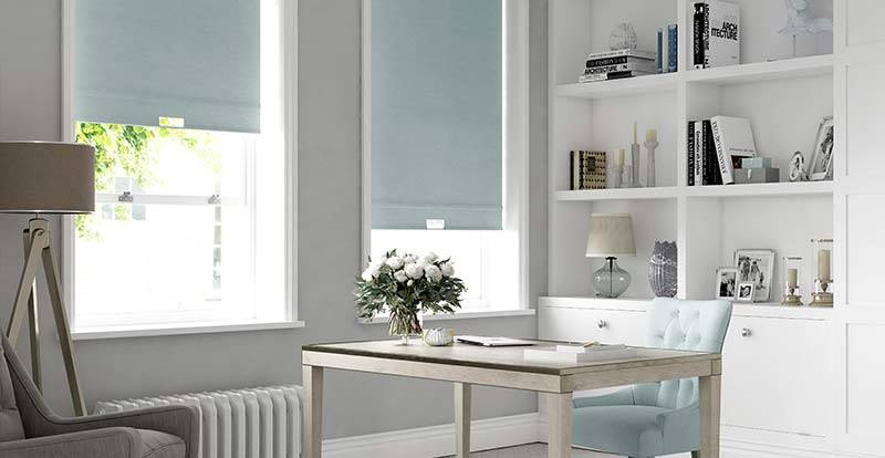 Home office with white shelving and blue roller blinds