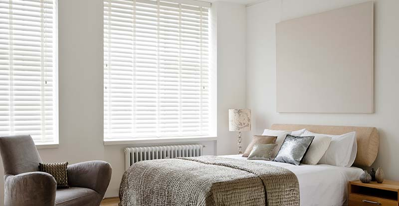 White wooden blinds with tapes in a bedroom