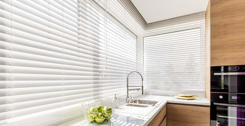 White wooden blinds in a big kitchen window