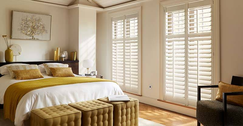 White full height shutters in a bedroom