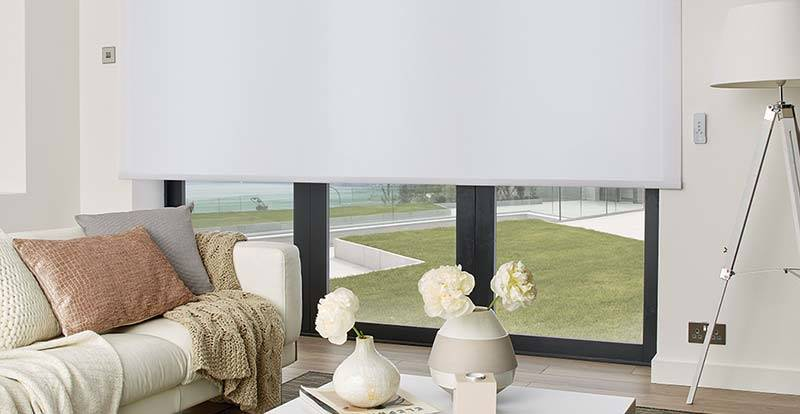 White roller blinds in a living room patio door