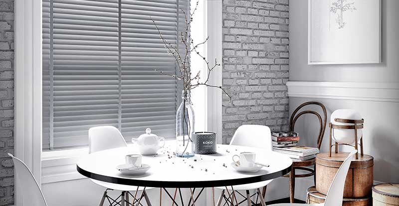 Grey taped faux wood blind in a dining room.