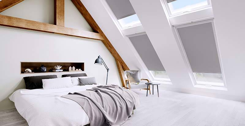 Grey skylight roller blinds in an attic bedroom