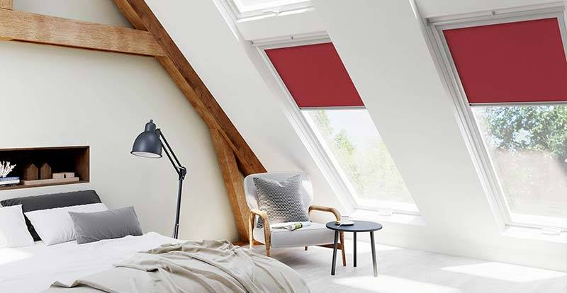 Attic bedroom with red skyroof roller blinds