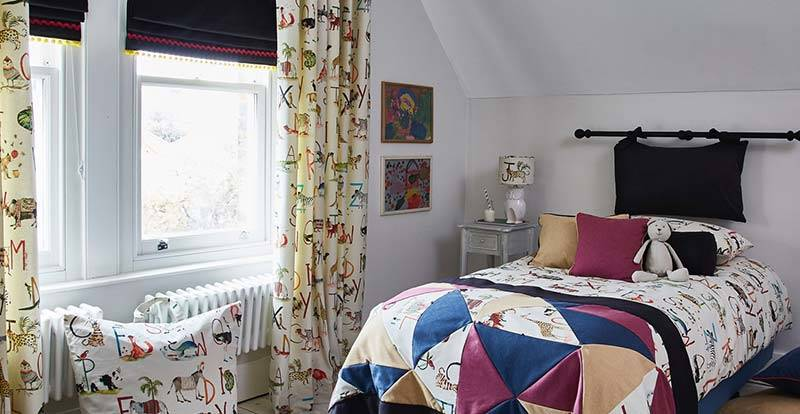 Children's room with blackout navy roman blind and patterned full length curtain