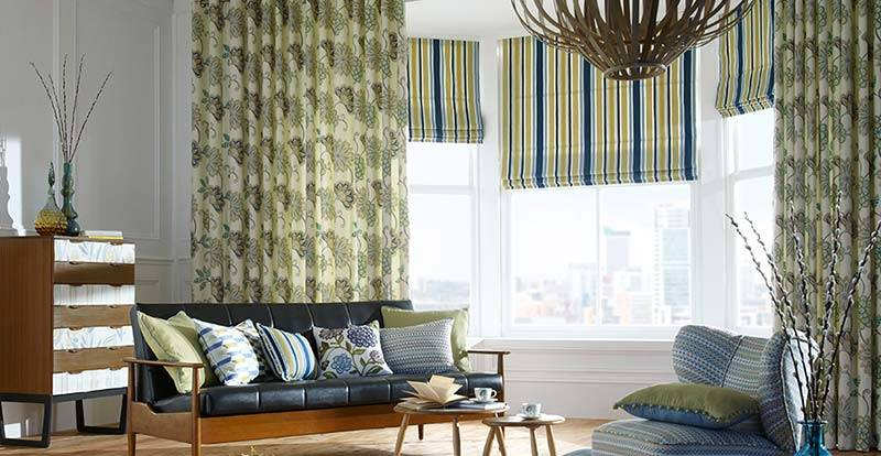 Big living room with striped blue roman blinds and patterned curtains