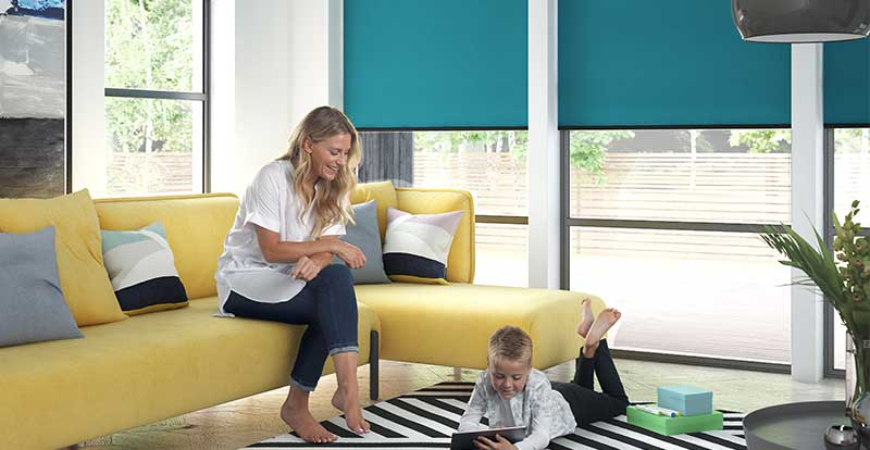 Lady and a boy playing in a living room with large electric roller blinds