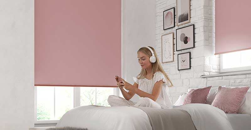Girl in a bedroom with large pink blackout roller blinds in windows