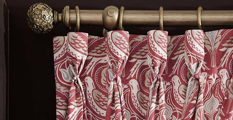 Close up of a patterned red curtain with a triple pinch heading