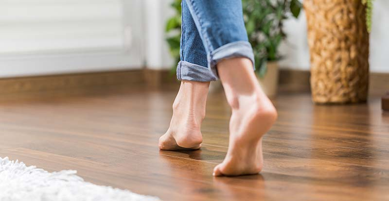 Close up of a barefoot woman walking in the house on the warm floor